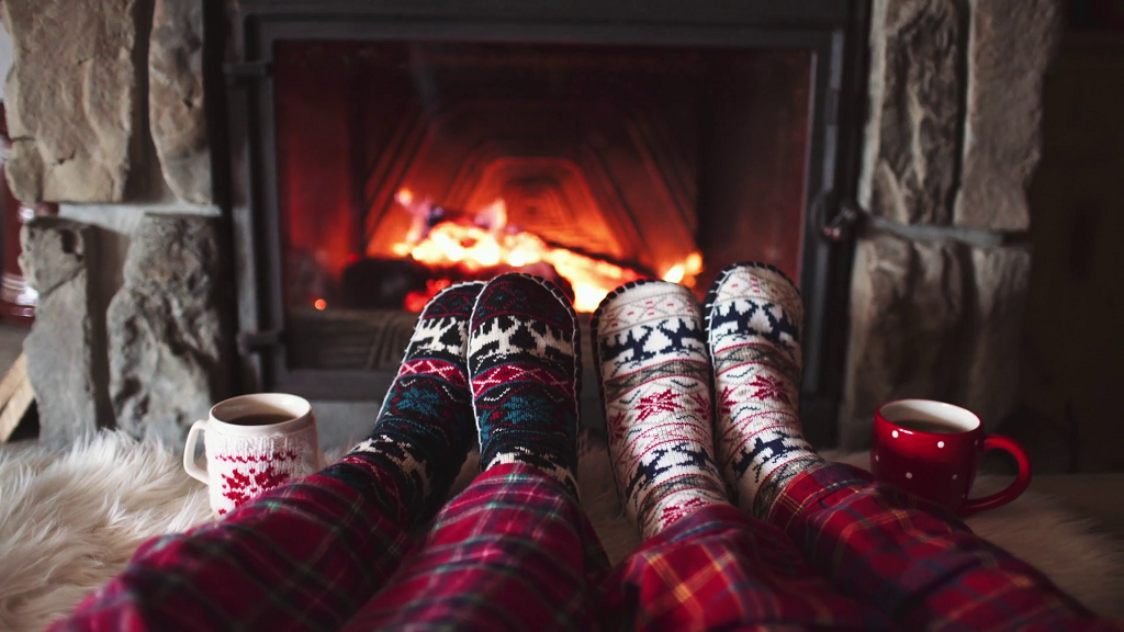 feet-in-woollen-socks-by-the-burning-christmas-cozy-fireplace-4k-couple-relaxes-by-warm-fire-with-cup-of-hot-drink-and-warming-up-their-feet-winter-and-christmas-holidays_mindre