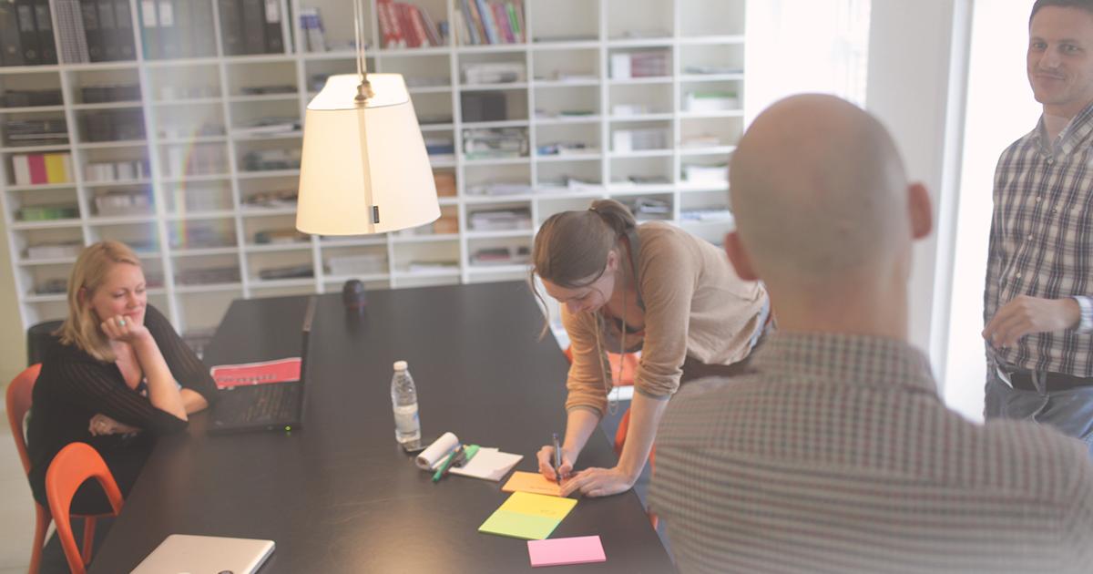 fire personer arbejder sammen på et projekt